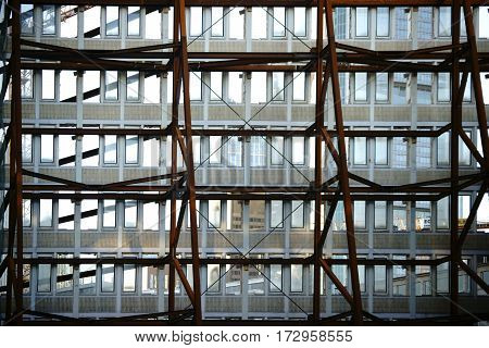 A heavy iron construction supports a single wall of a demolished high-rise building.