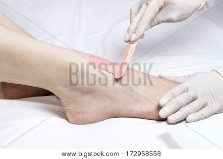 Process depilation female legs and hands in a beauty salon