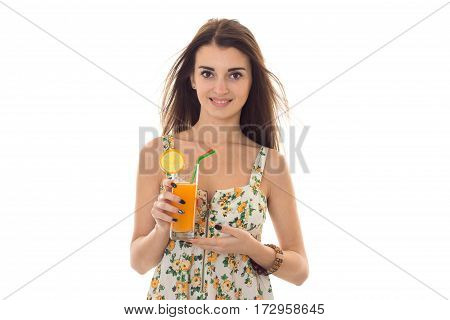 cheerful brunette woman in sarafan with floral patter drinks fresh orange cocktail and smiling on camera isolated on white