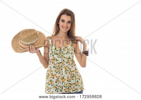 Happy brunette woman in sarafan with floral patter and straw hat posing and smiling on camera isolated on white