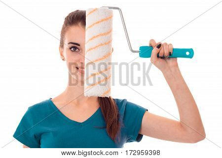 young beautiful brunette woman in uniform makes renovation with paint roller in her hands smiling on camera isolated on white