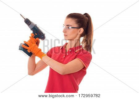 young pretty brunette woman in uniform makes renovation with drill in her hands looking away isolated on white