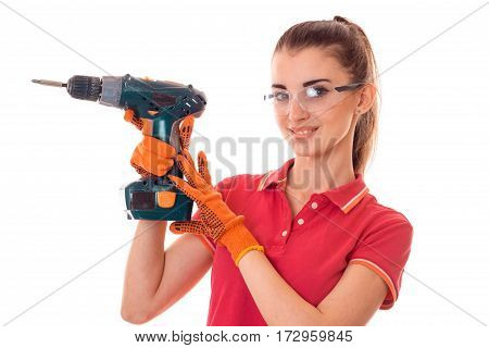 young happy brunette woman in uniform makes renovation with drill in her hands looking at the camera isolated on white