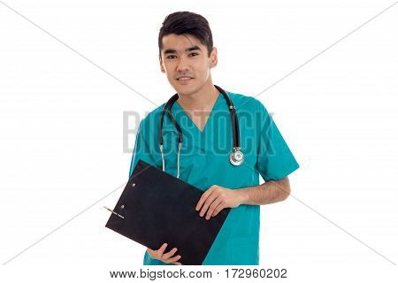 young pretty brunette male doctor in uniform with stethoscope make notes and looking at the camera isolated on white