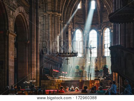 BAMBERG, GERMANY - Circa September, 2016:Beams of light pour in through chapel windows above altar and pews with large chandelier hanging overhead