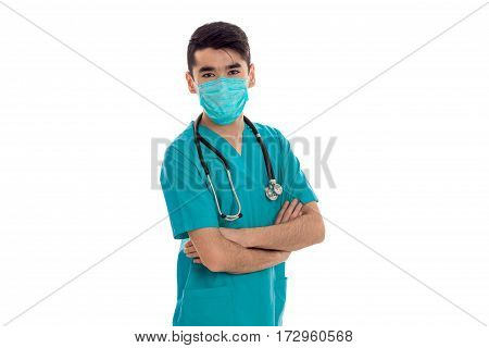 young handsome brunette male doctor in uniform and mask with stethoscope posing and looking at the camera isolated on white