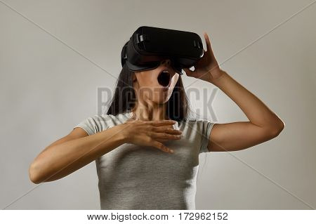 young attractive happy woman excited using 3d goggles watching 360 virtual reality vision enjoying cyber fun experience in vr simulation reality and new gaming technology isolated grey background