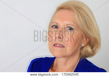 Portrait of a beautiful seventy year old lady with an angry expression. Studio shot, isolated on white.