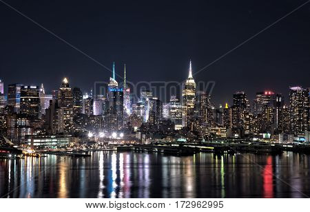 New York city skyline at night with building lights reflected in Hudson River