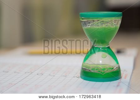 hourglass stand on a notebook in mathematics