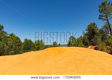 Orange ochre picturesque hills. Roussillon Provence France. Preserve natural dye production - ocher.