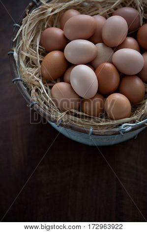 Fresh Farm Chicken Eggs in Wire Metal Basket on Wooden Table. Vertical, Close Up with Copy Space