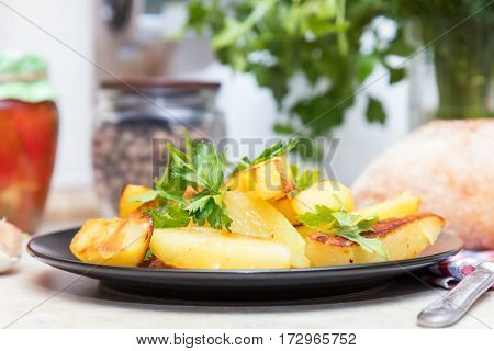Baked Fried Potatoes With Parsley In Black Plate
