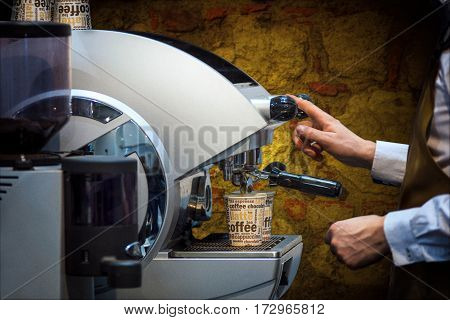The barman prepares coffee on a professional coffee machine in vintage style.
