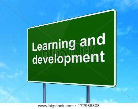 Learning concept: Learning And Development on green road highway sign, clear blue sky background, 3D rendering