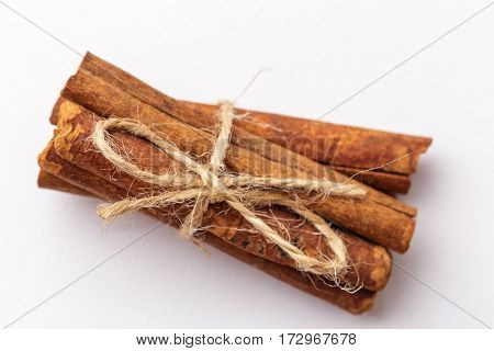 Macro or close up photo of cinnamon sticks bandaged by Twine on white background. Top view