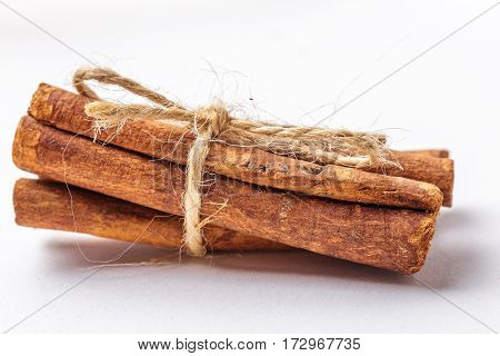 Macro or close up photo of cinnamon sticks bandaged by Twine on white background