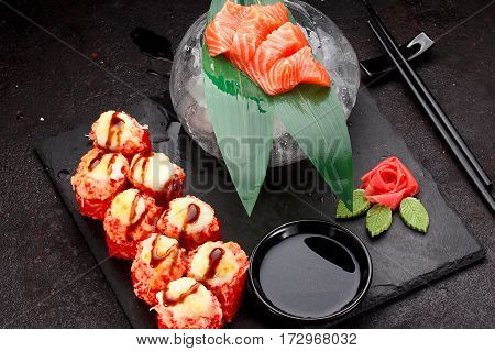 Japanese Cuisine. Baked (hot) Sushi Roll And Salmon Skewers On A Stone Plate Over Black Concrete Bac