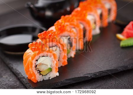 Japanese Cuisine. Salmon Sushi Roll On A Stone Plate Over Concrete Background.