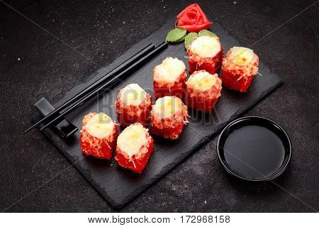 Japanese Cuisine. Baked (hot) Sushi Roll On A Stone Plate Over Black Concrete Background.