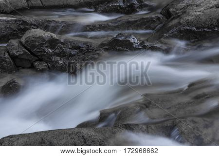 Rocks In Stream With Smooth Flowing Water.