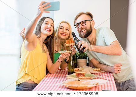 Young friends dressed casually in colorful t-shirts making selfie photo with pizza and beer at home