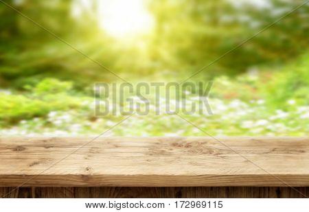 Wooden desk on bright sunny bokeh background for spring or summer
