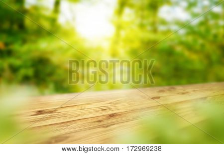 Empty wooden desk on sunny bokeh background to present and show product