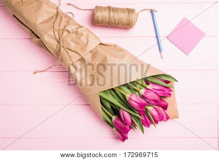 Purple tulip bouquet in woman hands on pink background. Top view over pink wooden table