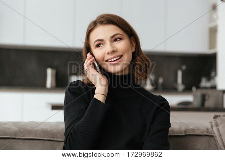 Picture of young happy woman sitting at kitchen. Talking by mobile phone.