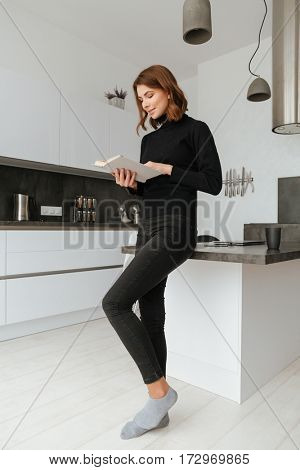 Photo of young pretty lady dressed in black sweater standing at home indoors. Reading book.