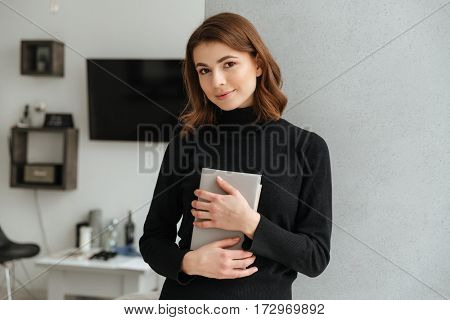 Image of young pretty lady dressed in black sweater standing at home indoors. Holding book.