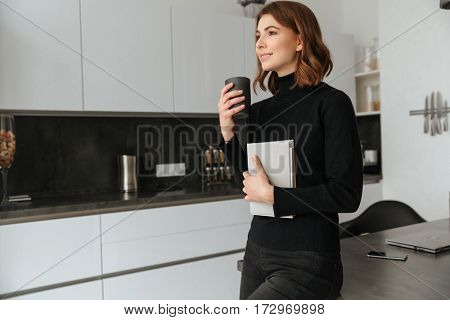 Image of young smiling woman dressed in black sweater standing at home indoors. Reading book.