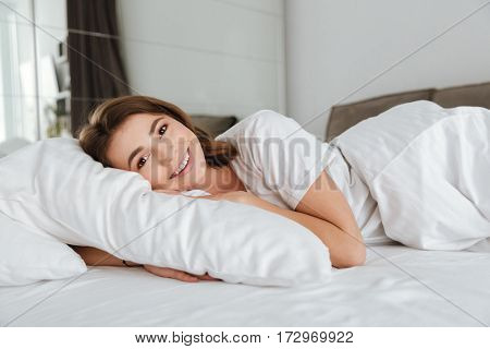 Image of young cheerful woman dressed in white t-shirt lies in bed at home indoors. Looking at camera.
