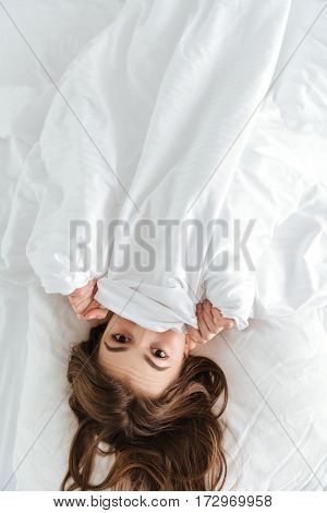 Picture of young happy woman dressed in white t-shirt lies on bed at home indoors.