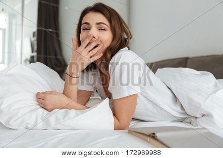 Picture of young happy woman dressed in white t-shirt lies in bed at home indoors. Looking at camera and yawning.