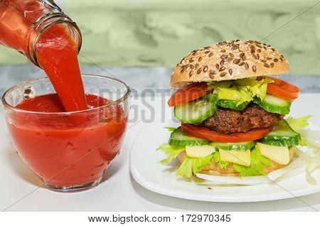Great Burger and tomato juice poured into glass Cup. Cup