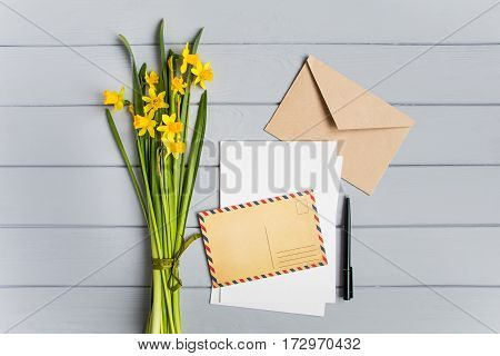Letter postcard envelope and daffodils bouquet on grey wooden background. Wedding invitation cards or love letter. Romantic holiday concept top view flat lay overhead view