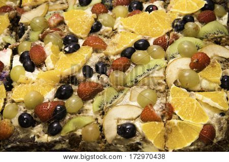 assorted cake decorated with slices of orange and strawberry kiwi grapes