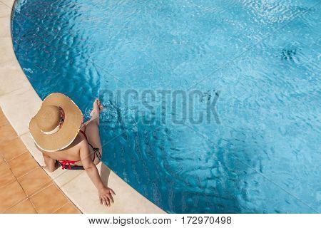 Woman sitting in the edge of swimming pool enjoying suntan