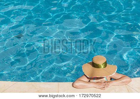 Woman enjoying suntan at the swimming pool