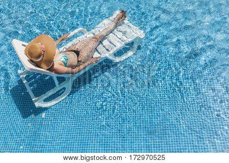 Woman having sunbathing at the swimming pool