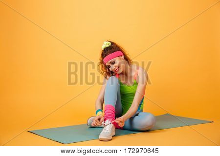 Happy charming young sportswoman sitting on mat and tying shoelaces