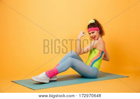 Smiling beautiful young sportswoman doing exercises for abdominal muscles on mat over yellow background