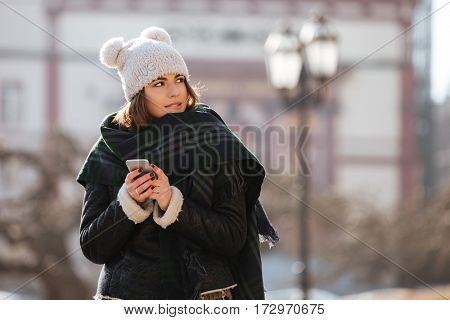 Pensive attractive young woman using mobile phone walking in the city