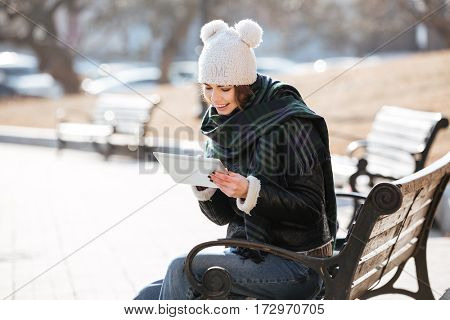 Smiling pretty young woman sitting on bench and using tablet outdoors