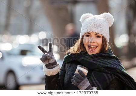 Cheerful young woman drinking coffee and showing peace sign outdoors in autumn