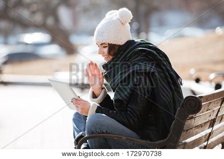 Cheerful charming young woman having video conference using tablet outdoors