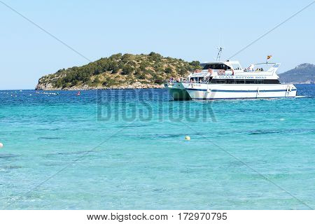 MALLORCA SPAIN - JUNE 1: The recreation motor yacht with tourists on tour to Cape Formentor on June 1 2015 in Mallorca Spain. Up to 60 mln tourists is expected to visit Spain in year 2015.