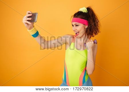 Cheerful charming young sportswoman working out with dumbbell and making selfie using smartphone
